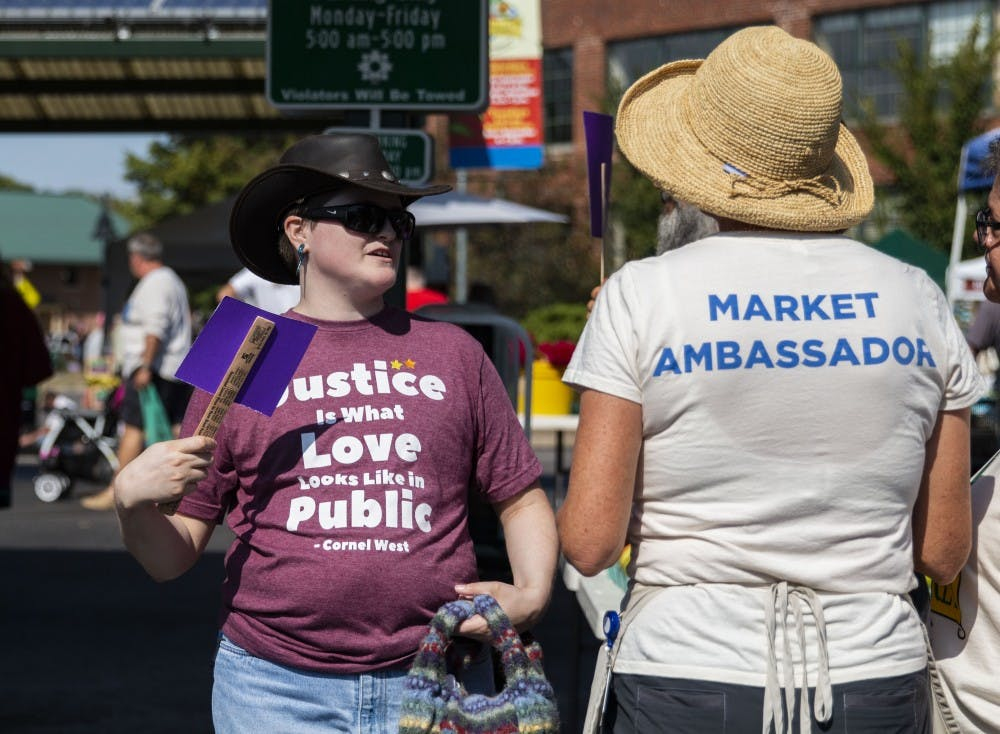 <p>Members of the Purple Shirt Brigade boycott Schooner Creek Farm with different-sized pieces of purple paper on sticks Sept. 28 at the Bloomington Community Farmers' Market. The group said the items were fans, but their resemblance to signs made them toe the line on whether they were allowed to be carried around the market.</p>