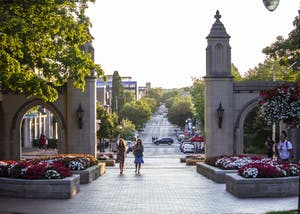 People walk through the Sample Gates on June 27 near Franklin Hall. The Sample Gates are considered a gateway to IU's campus.