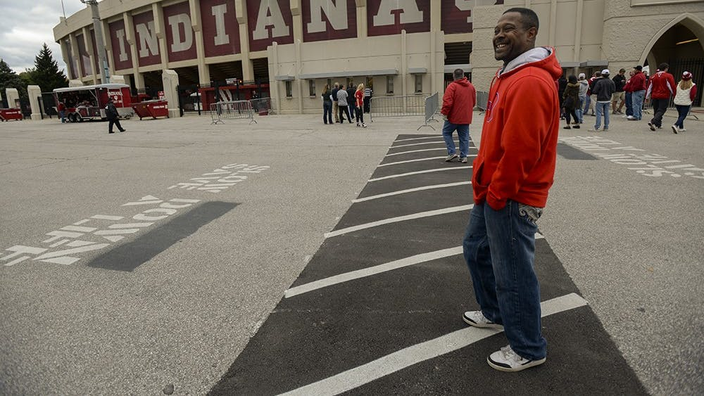 Jeffery walks by Memorial Stadium to get to his usual street corner. University policy prohibits ticket scalping on campus grounds, so when he walks through the parking lots he abides by the policy and places his sign under his shirt, until he reaches the south side of 17th St. The more he looks like a casual fan, the less he will be hassled while on campus gronds.