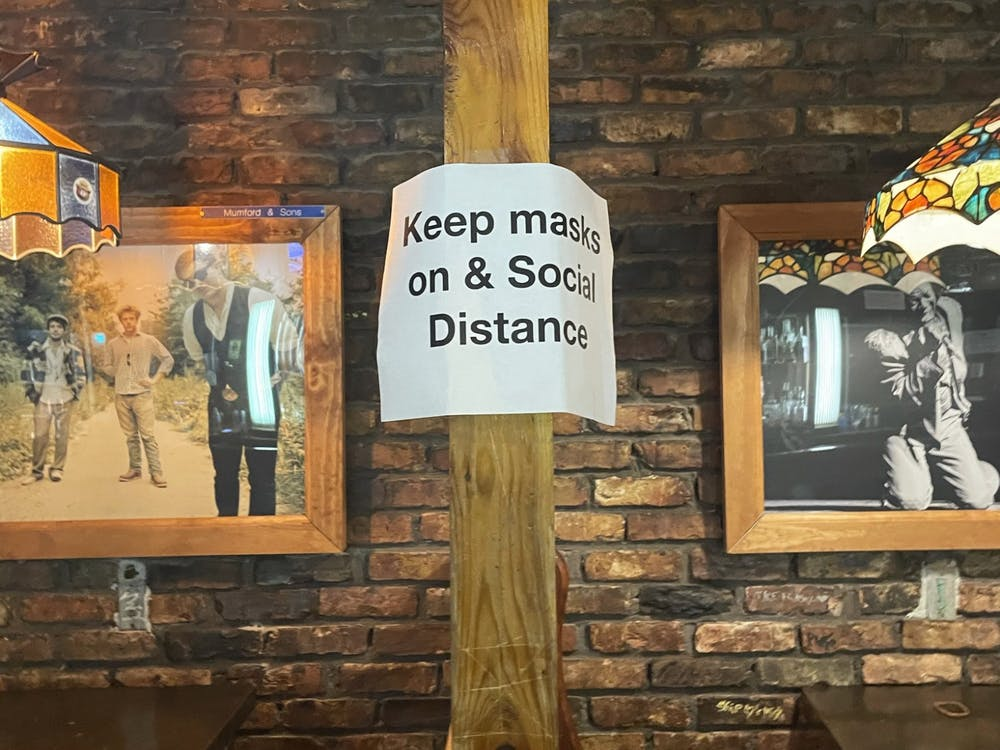 """A sign inside the Bluebird reads """"Keep masks on & Social Distance."""" These signs were placed throughout the venue, but were largely ignored on Feb. 13."""