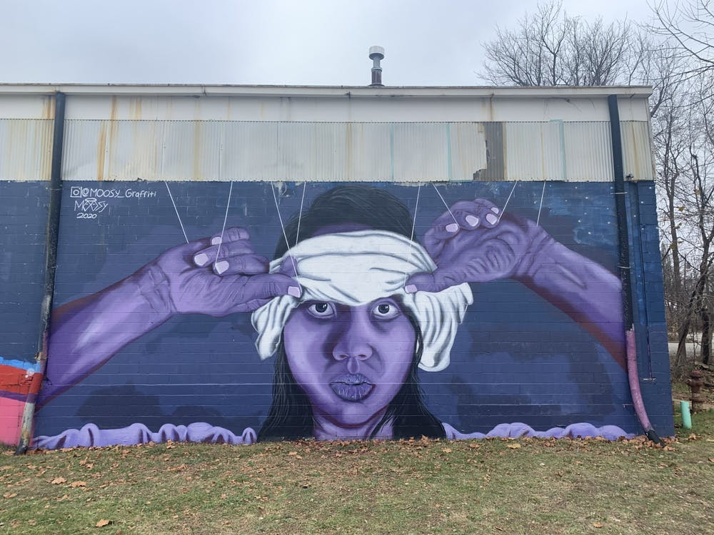 <p>Sophomore Trenton Musch's mural is pictured Nov. 20 at the Warehouse. The face in the mural is based off of Shun Lin, his neighbor and friend.</p>