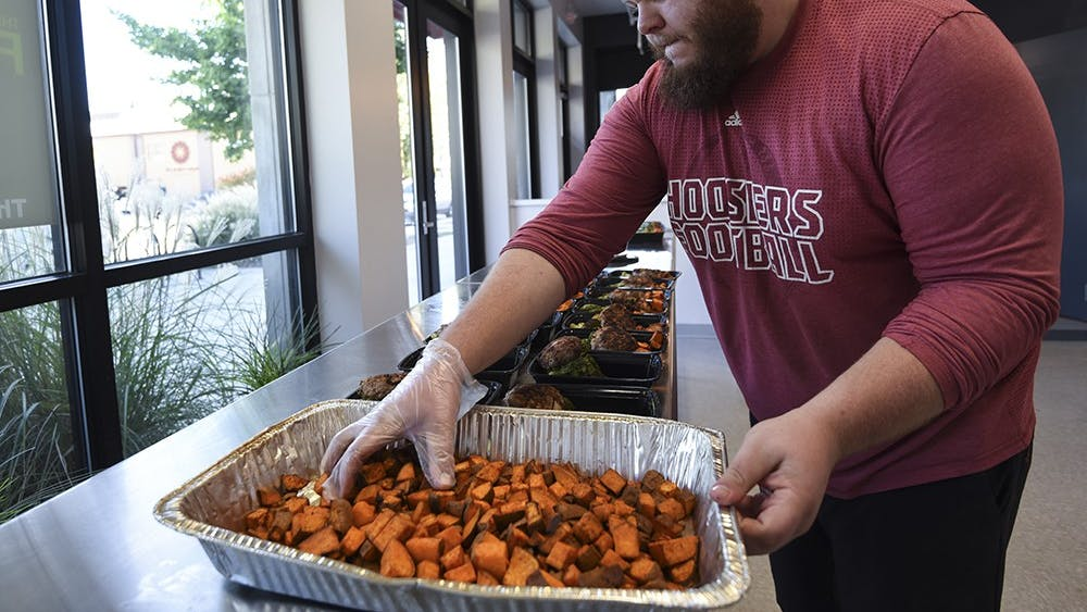 Travis Leonard, assistant kitchen manager, assembles meals in The Fresh Fork on Thursday. The Fresh Fork is a custom meal ordering service that delivers food to Willkie and Eigenmann residence halls and to Bloomingfoods.