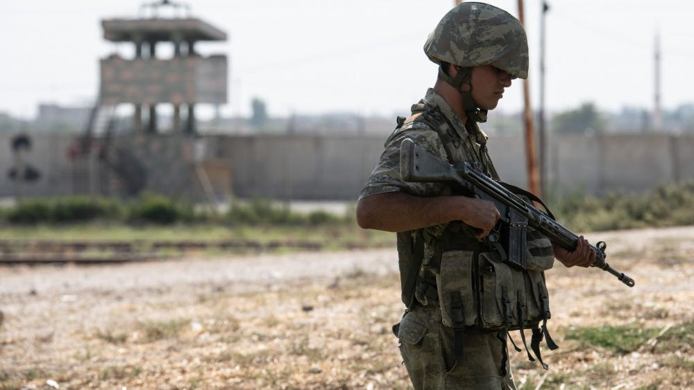 Turkish soldiers stand guard on the Turkish side of the border between Turkey and Syria on Oct. 9 in Akcakale, Turkey. Military personnel and vehicles gathered near the border ahead of a campaign to extend Turkish control of more of northern Syria, a large swath of which is currently occupied by Syrian Kurds, whom Turkey regards as a threat.