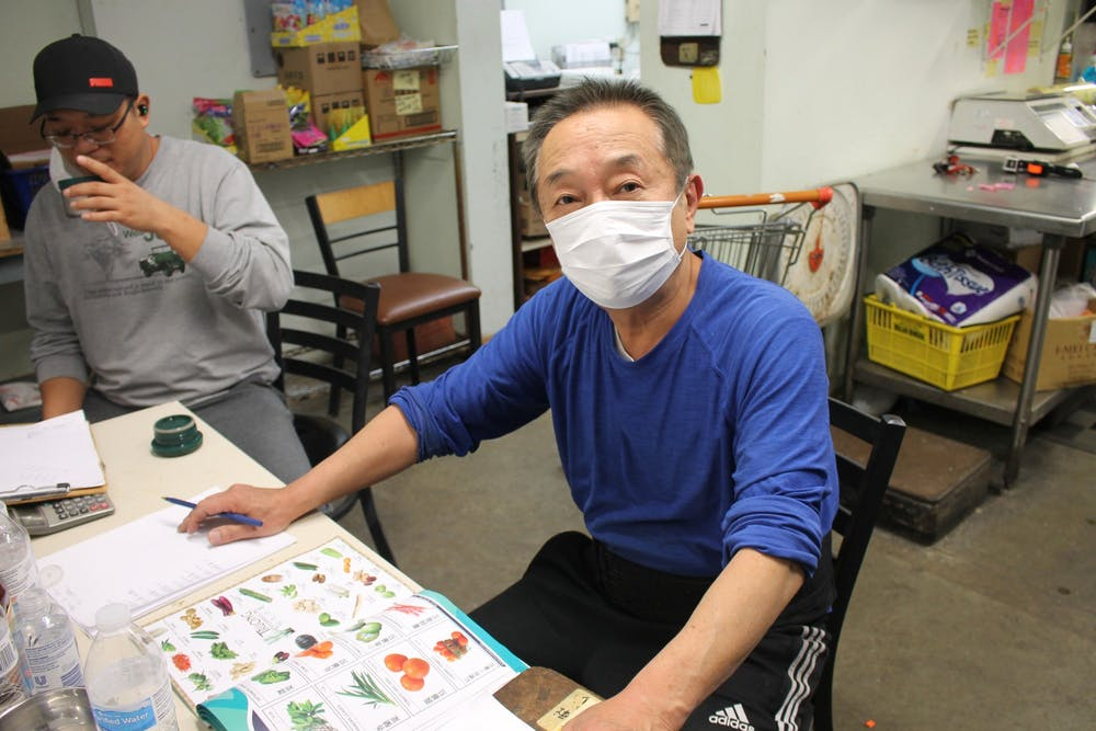 <p>Mark Li, owner of B-Town International Market, works in his store on Tuesday evening. Bloomington's Asian business owners have faced challenges growing their businesses and maintaining their sales levels during the COVID-19 pandemic. </p>