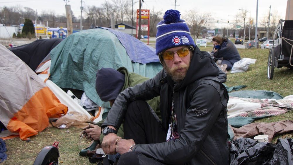 Bloomington resident Daniel Floyd sits by his tent Jan. 14 in Seminary Park. Bloomington City Council members drafted a new ordinance that provides protection for people experiencing homelessness. The ordinance will not be discussed at a council meeting until at least mid-February.