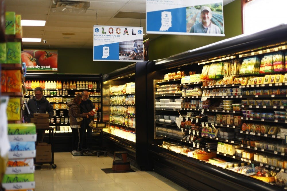 <p>Customers and an employee look at the products offered at Bloomingfoods on April 15, 2019, in Bloomington. </p>