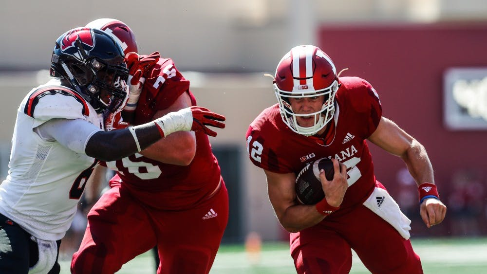 Sophomore quarterback Peyton Ramsey rushes the ball up the field during the first quarter of play against Ball State on Saturday at Memorial Stadium