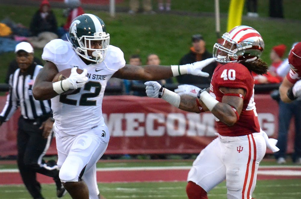 Michigan State running back Delton Williams stiff arms IU sophomore safety Antonio Allen in the Hoosiers' homecoming game against Michigan State on Saturday at Memorial Stadium.