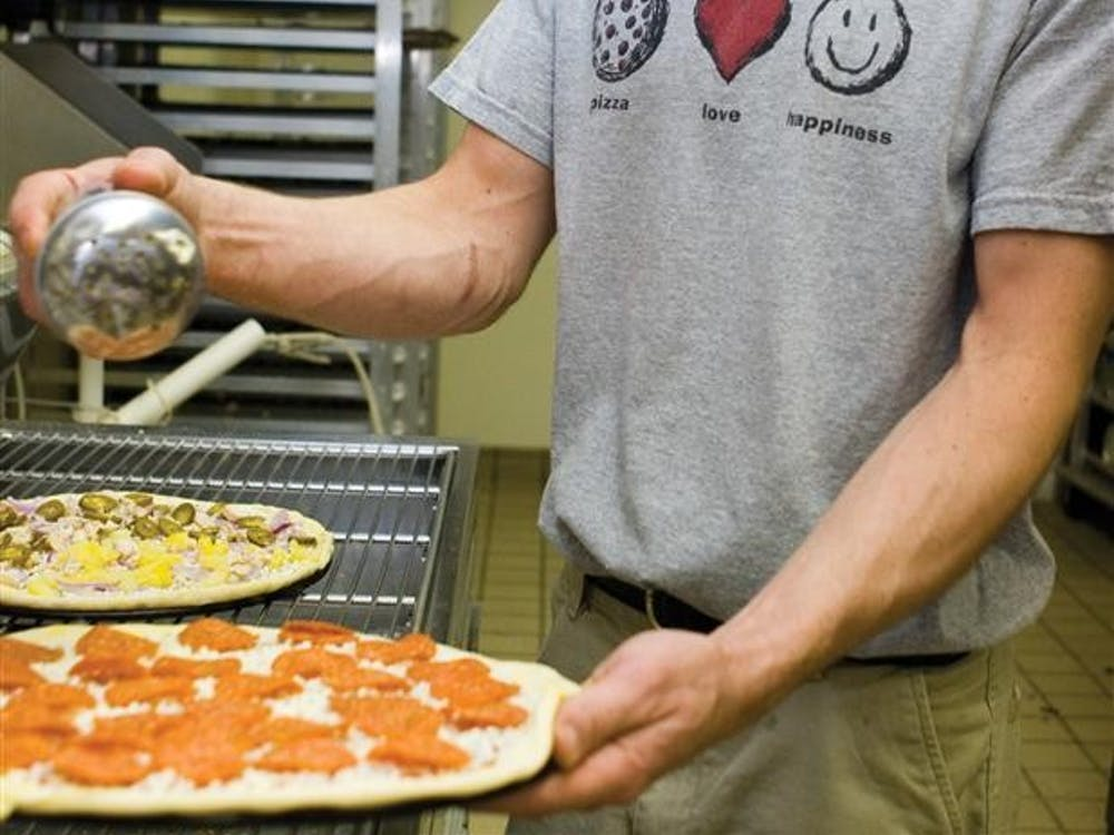 Pizza Express employee John Reidy puts the final touches on a pizza before putting it in the oven Thursday, May 3, 2007 at the Pizza Express on East Tenth Street.