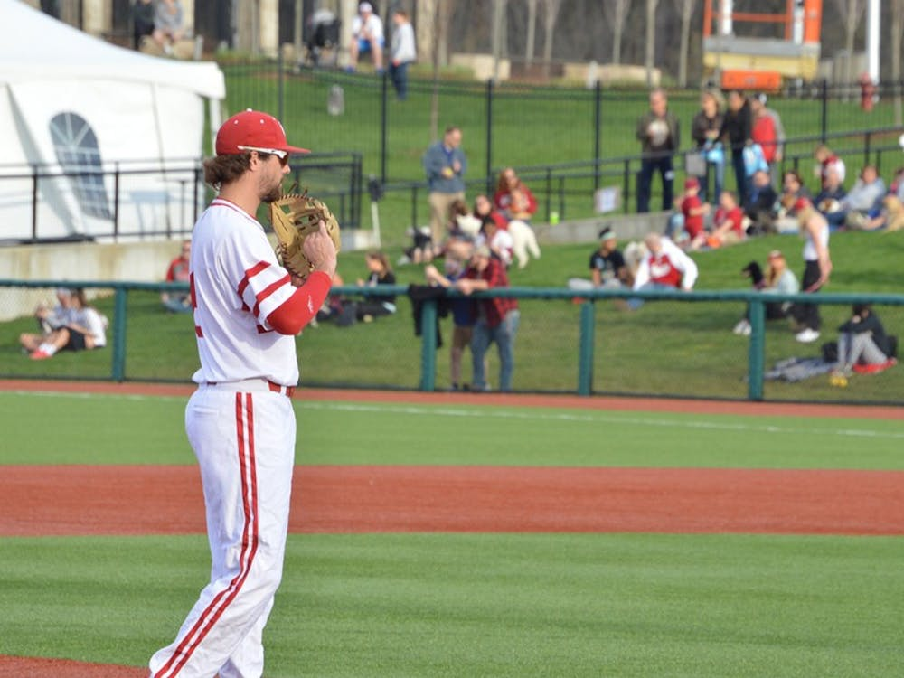 Sophomore Luke Miller dusts off his glove after stopping a ground ball Tuesday evening during IU's game against Ball State. Miller had a 6-RBI weekend against the Michigan Wolverines.