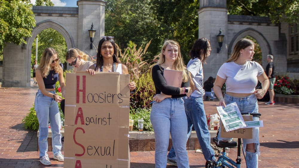 IU sophomore Aanya Jain, senior Grace Yoder and sophomore Grace Sarrazin stand Oct. 8, 2021, outside the Sample Gates in protest of the IU Police Department policy not to list the location of reported sexual assualts on the crime logs.