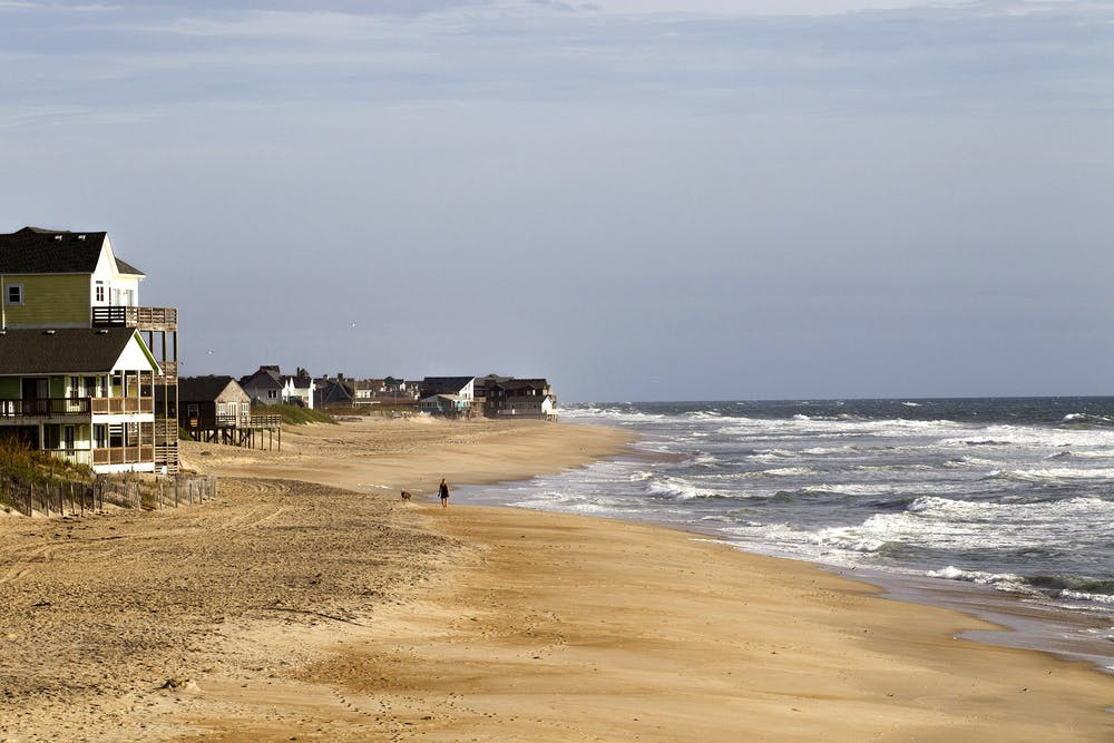 <p>A woman walks with her dog Sept. 5, 2019, in Rodanthe, North Carolina. A California family&#x27;s beachfront property is being returned to them after being taken nearly 100 years ago.</p>