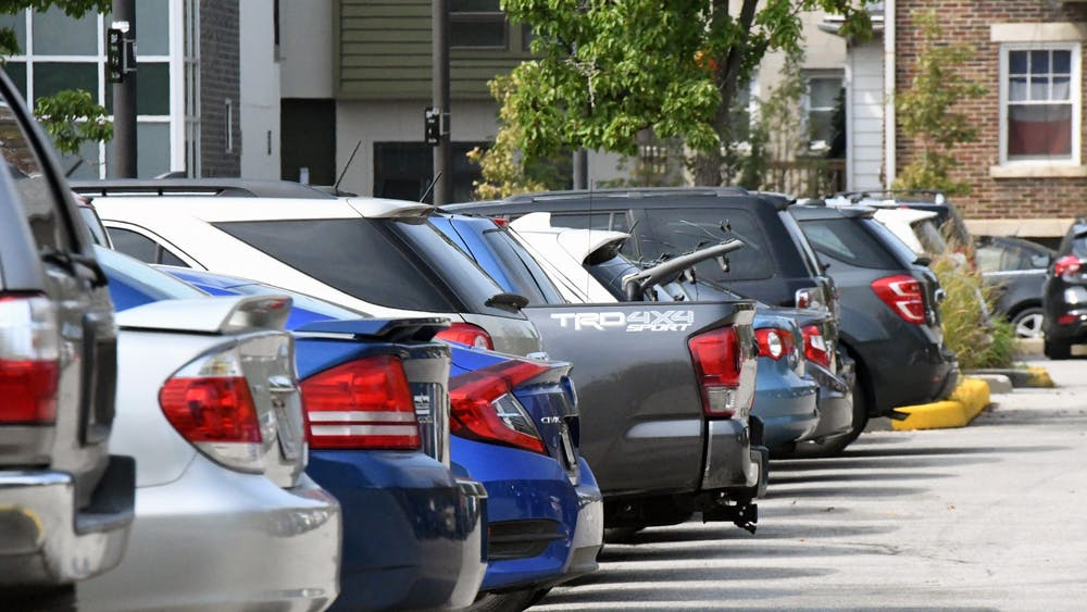 Parked cars are lined up in a parking lot on East Sixth Street. IU employees now have the option to purchase multiyear parking permits.