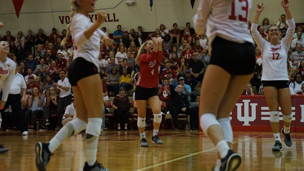 Sophomore defensive specialist Bayli Lebo celebrates with her teammates after scoring a point during a long rally against Northwestern on Sept. 21 in the University Gym. Lebo leads the team in digs this season.