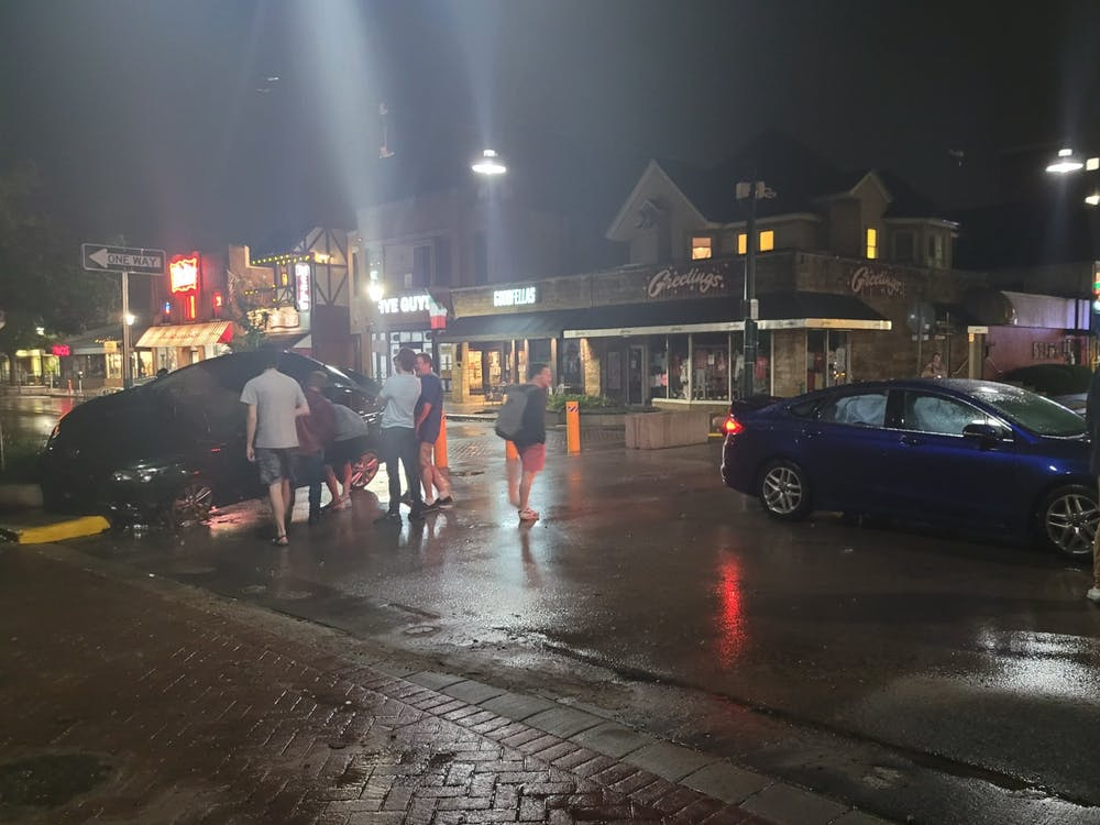 People walk June 18 on Kirkwood Ave after the flood water went down.