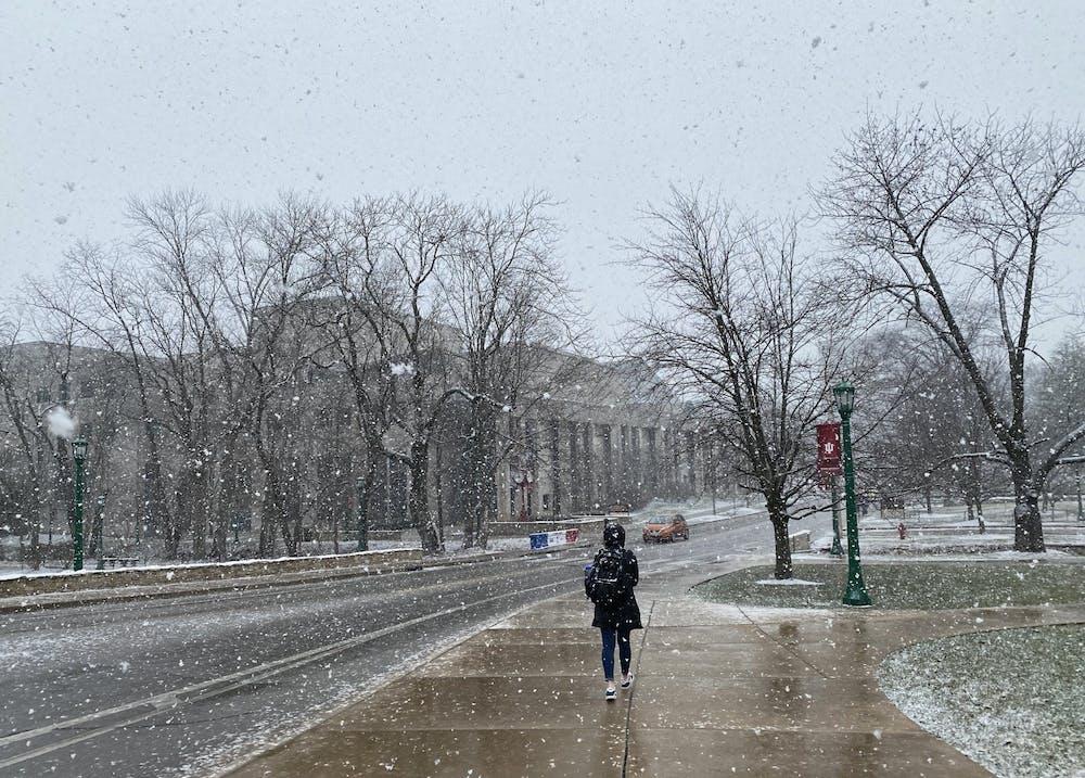 <p>An IU student walks through the snow Feb. 9 on Jordan Avenue. The Evan Scholars and Sigma Delta Tau houses began their quarantines Monday.</p>