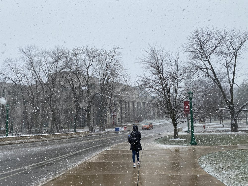 An IU student walks through the snow Feb. 9 on Jordan Avenue. The Evan Scholars and Sigma Delta Tau houses began their quarantines Monday.