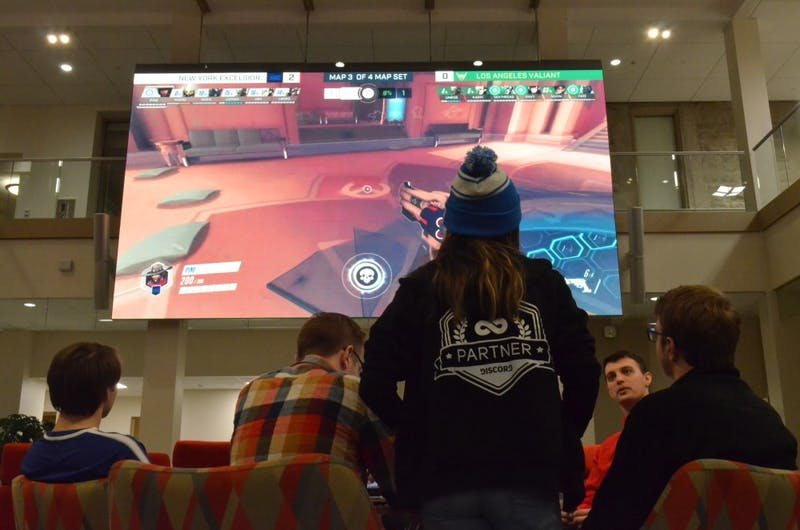 "Members of IU's esports team gather in Franklin Hall to attend the Winter Esports Expo. On the large screen in the Media Commons of Franklin Hall, professional esports teams from New York City and Los Angeles battle it out in the video game ""Overwatch."""