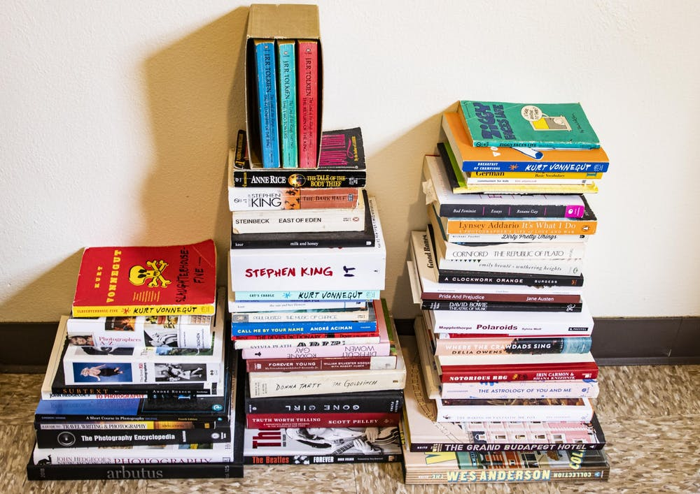 <p>Three stacks of books sit on the ground in a University East apartment.</p>