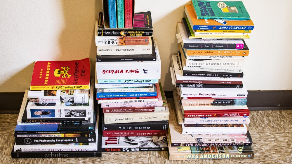 Three stacks of books sit on the ground in a University East apartment.