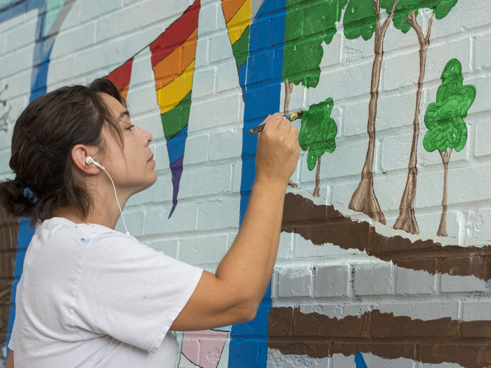 Eva Rholfing Allen paints a section of the mural in 2017 in Peoples Park. A release from the Bloomington Arts Commission encourages artists to submit proposals for new artwork which will be located near downtown Bloomington at the Trades District Garage.