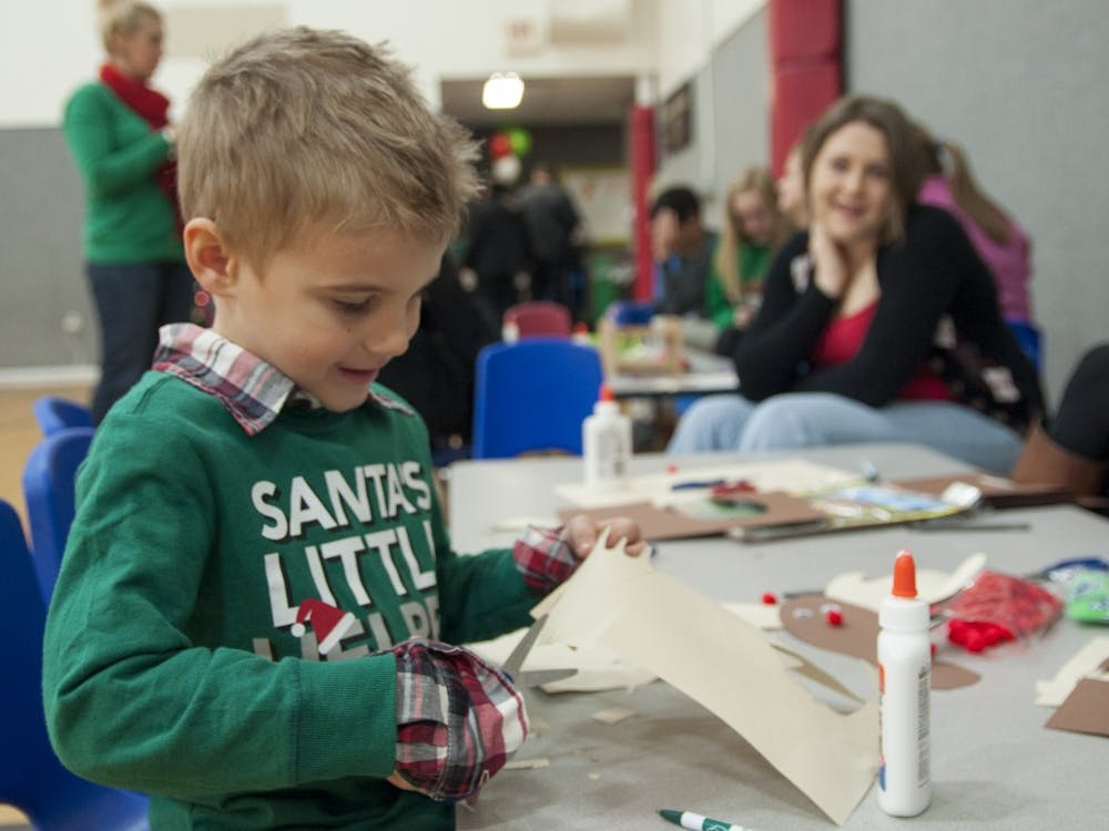 Four-year-old Parker Foust cuts paper to make a reindeer craft during Breakfast with Santa in 2013 at the YMCA. The YMCA had to shut down their childcare program because they could no longer afford the financial subsidies required to remain a licensed child care center.