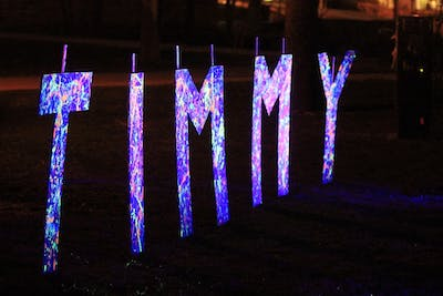 """A glow-paint colored sign that reads """"Timmy"""" sits in Dunn Meadow. Students gathered April 12, 2018, to run and enjoy live music during the Timmy Glow Run, sponsored by Timmy Global Health at IU. This year's Timmy Glow Run is expected to be rescheduled for April 25 in Dunn Meadow."""