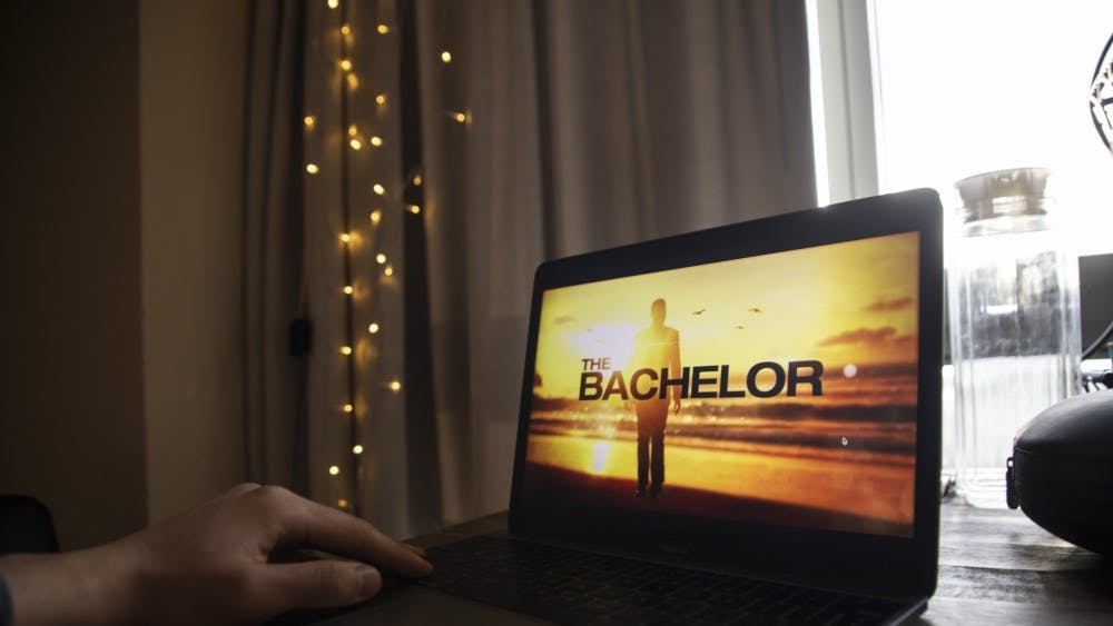 """A student watches """"The Bachelor"""" on his laptop April 8 in his apartment. """"The Bachelor,"""" an American dating and relationship reality television series, debuted in 2002."""