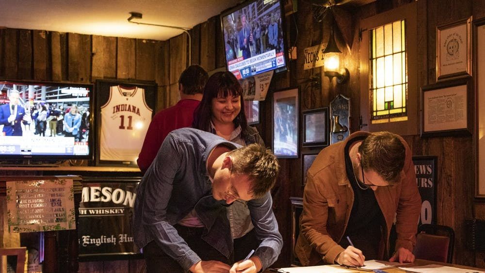 """IU second year law students Alex Busse and Matt Ritter sign Iowa Caucus watch party attendance sheets Feb. 3 at Nick's English Hut. """"I am feeling the Bern,"""" Busse said."""