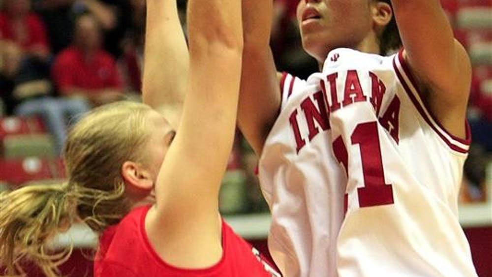 IU senior forward Whitney Thomas goes up for a basket over Southern Indiana's Courtney Perry during a game on Saturday at Assembly Hall. IU won 93-49.