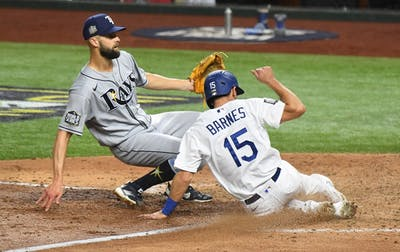 The Los Angeles Dodgers Austin Barnes scores in front of Tampa Bay Rays pitcher Nick Anderson on a wild pitch in the sixth inning during Game 6 of the World Series, on  Oct. 27 at Globe Life Field in Arlington, Texas.