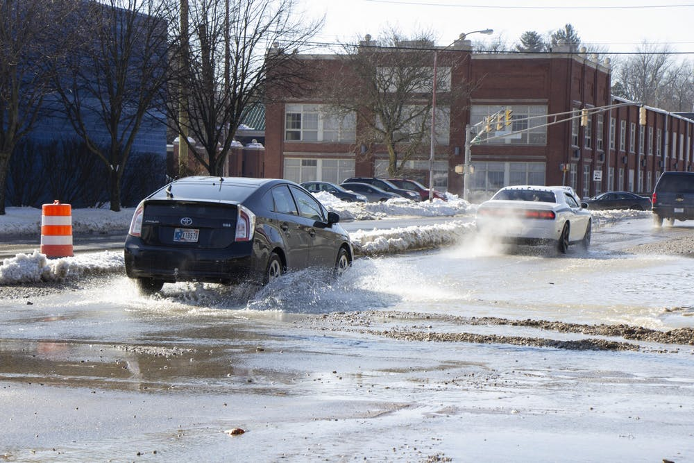 <p>A car drives through water on Third Street. Water exploded from the pavement around 1 p.m., a Holly McLauchlin, City of Bloomington communications specialist, said.</p><p></p>