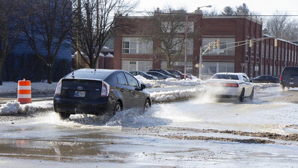 A car drives through water on Third Street. Water exploded from the pavement around 1 p.m., aHolly McLauchlin, City of Bloomington communications specialist, said.