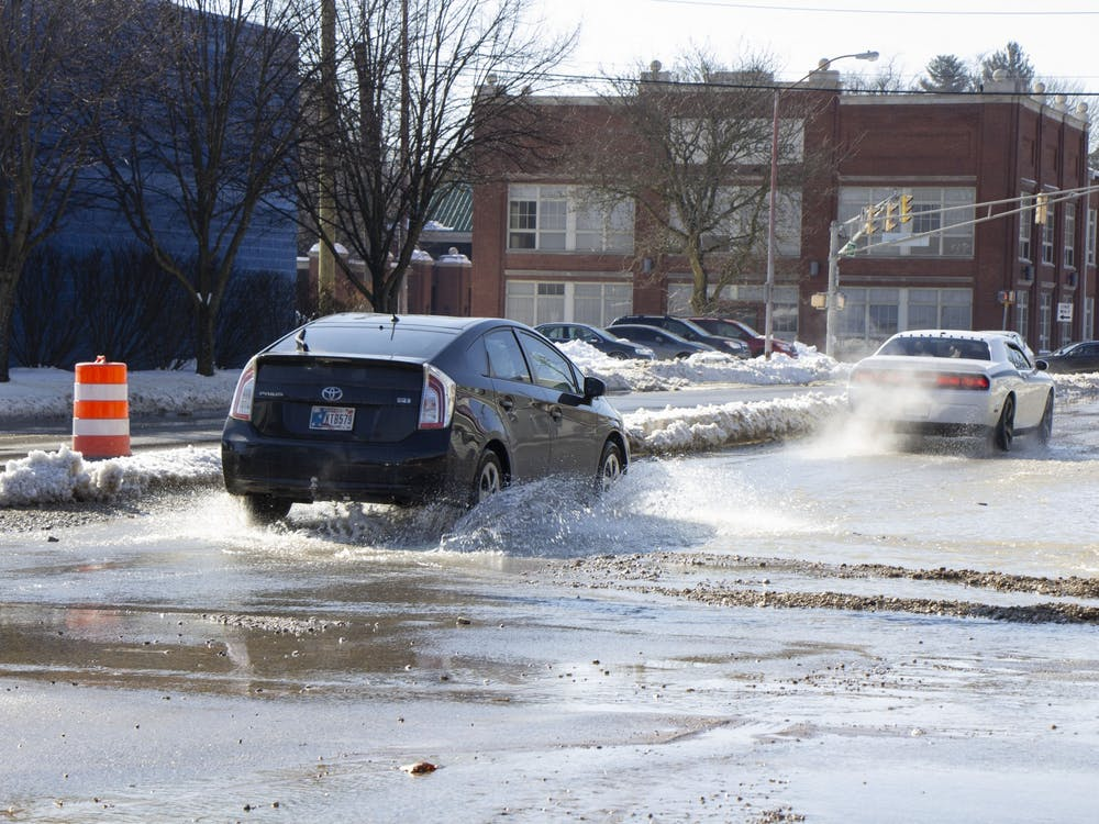 A car drives through water on Third Street. Water exploded from the pavement around 1 p.m., a Holly McLauchlin, City of Bloomington communications specialist, said.