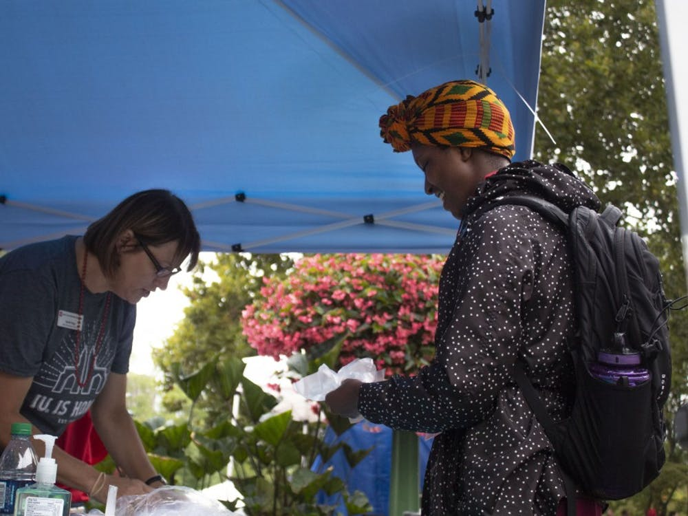 Junior Antonnia Laderson picks up her name tag and gloves from the volunteer tent last Thursday at CultureFest. She volunteered to help with preparing food at the Neal-Marshall Black Culture Center.