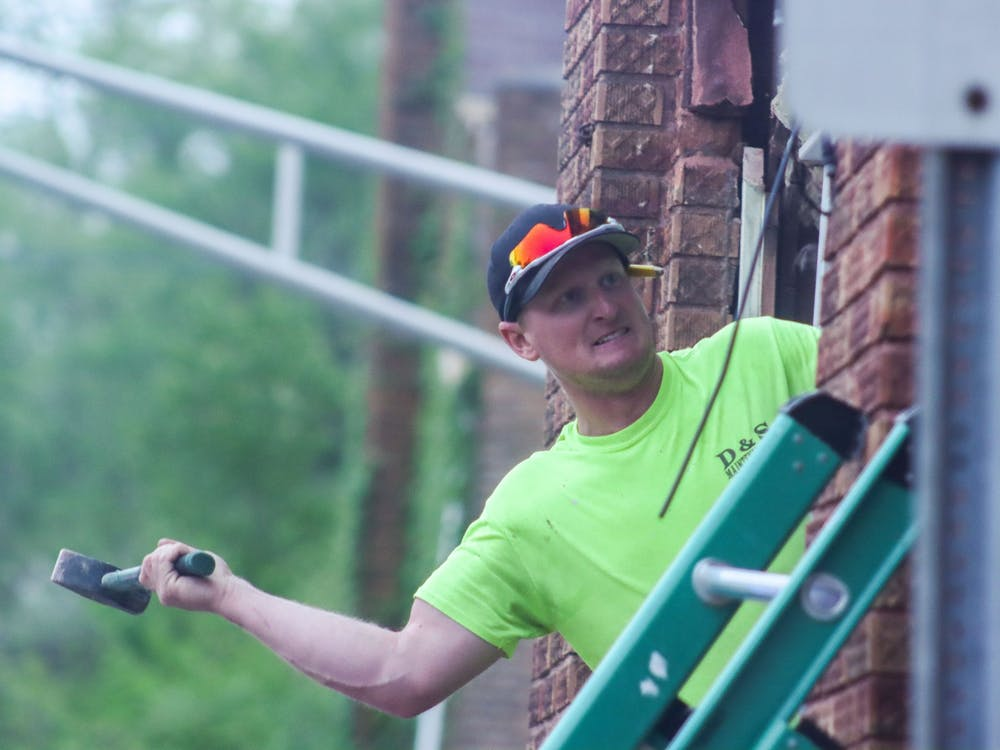 Tyler Deckard of D & S Maintenence Inc. uses a sledge hammer to knock down bricks Sunday night. Police were not offering information about how or why a U-Haul truck crashed into Evil by the Needle on Sunday evening.