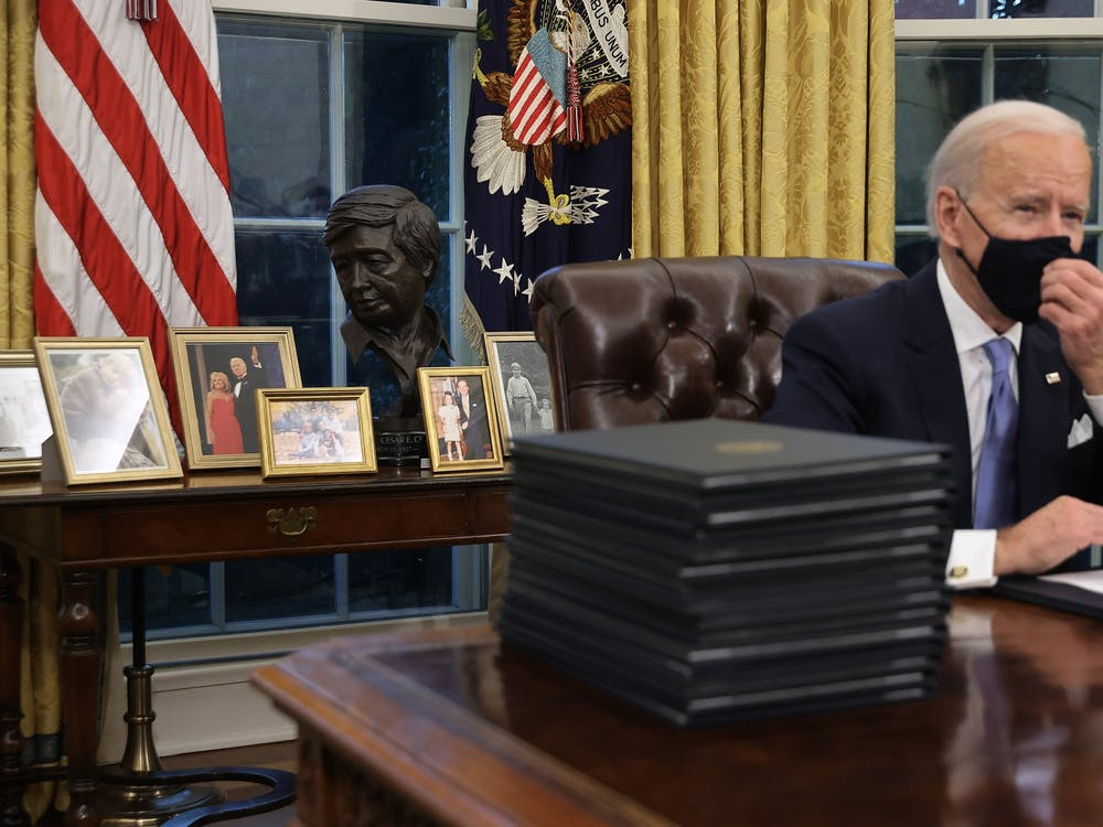 President Joe Biden prepares to sign a series of executive orders at the Oval Office hours after his inauguration on Jan. 20, in Washington. Biden has signed orders to address advancing racial equity and support for underserved communities and economic relief for COVID-19.