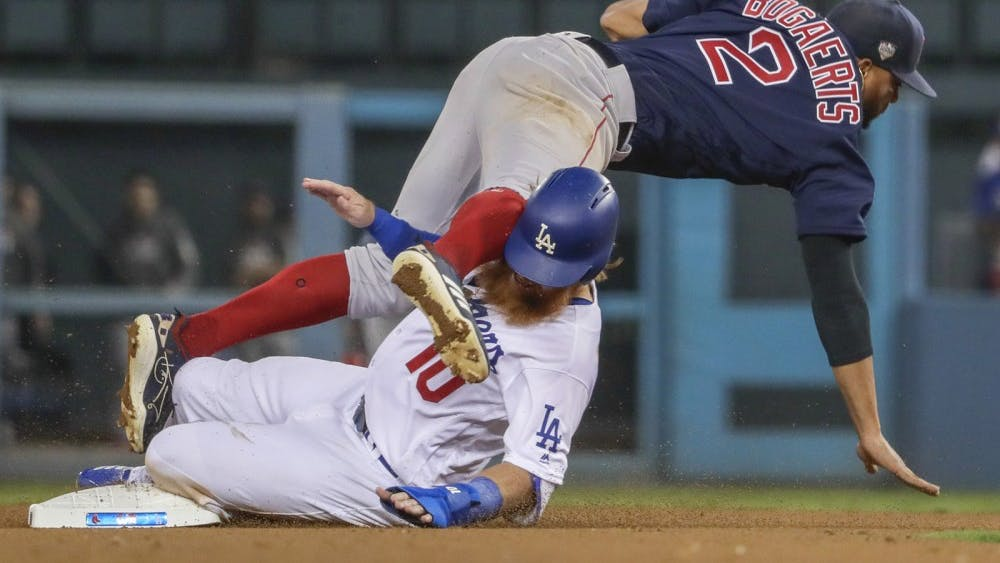 The Los Angeles Dodgers' Justin Turner is out at second in a failed bid to break up a double play as Boston Red Sox shortstop Xander Boegaerts tumbles over him Oct. 26, 2018 during Game 3 of the World Series at Dodger Stadium in Los Angeles.