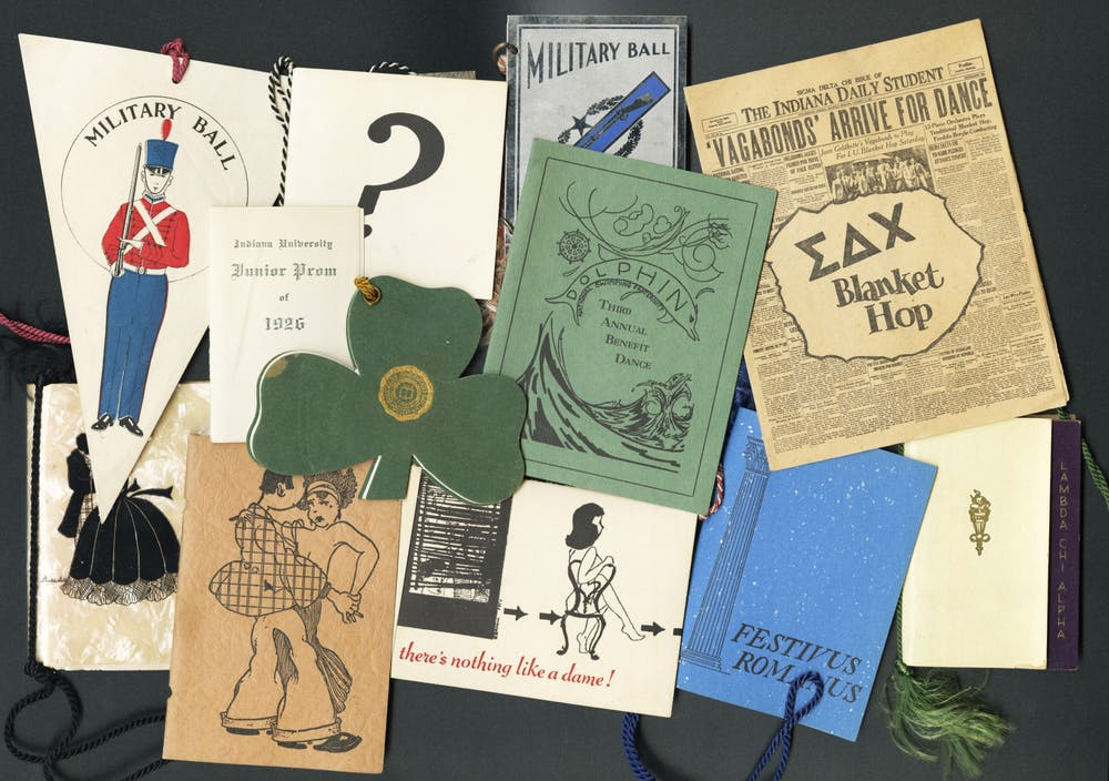 <p>A photo of dance cards from the late 1800s to early 1950s lay on a table. They were used for the women to check their availability and create a list of upcoming dances. </p>
