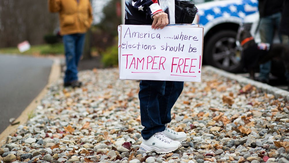 "A woman holds a sign during a ""Stop the Steal"" car rally Nov. 22 in Long Valley, New Jersey. Almost all of President Donald Trump's lawsuits regarding the election, after weeks of baseless claims of election fraud, have been dismissed or withdrawn from court as Michigan, Pennsylvania, Arizona, Wisconsin and Georgia have all certified their election results as accurate and free of fraud, with President-elect Joe Biden winning all five states."
