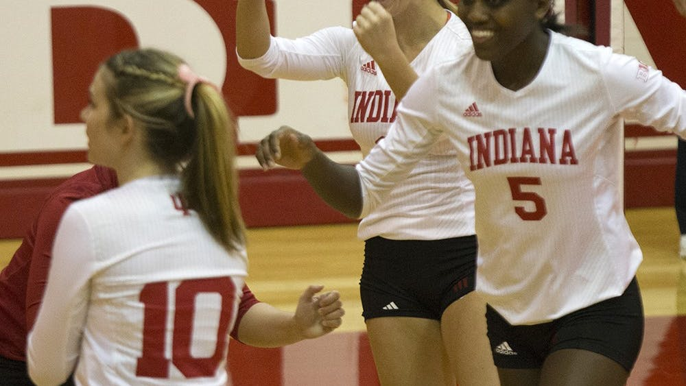 Sophomore Taylor Lebo and sophomore Jazzmine McDonald cheer after a point is won during the team's game versus Minnesota on Wednesday in Bloomington.