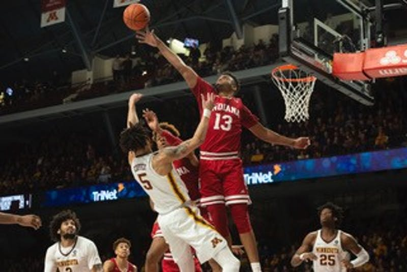 Senior forward Juwan Morgan swats Amir Coffey's shot from the basket during the game against Minnesota on Feb. 16. The Gophers won 84-63.