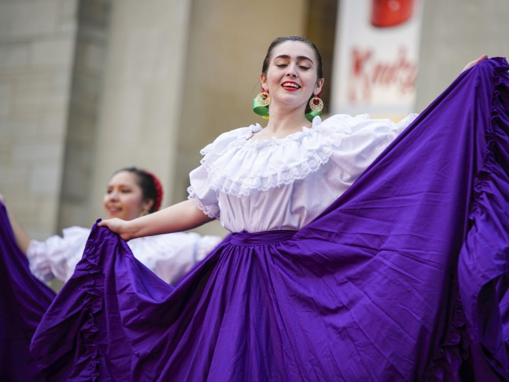 Third-year graduate student Patty Gonzalez of Ballet Folklorico performs as the group begins to draw a crowd during the Hispanic Heritage Month-themed First Thursday festival in the Fine Arts Plaza. Inclement weather forced acts such as the IU Soul Revue and IU Contemporary Dance to take their performances to Neal-Marshall Grand Hall and the School of Public Health.