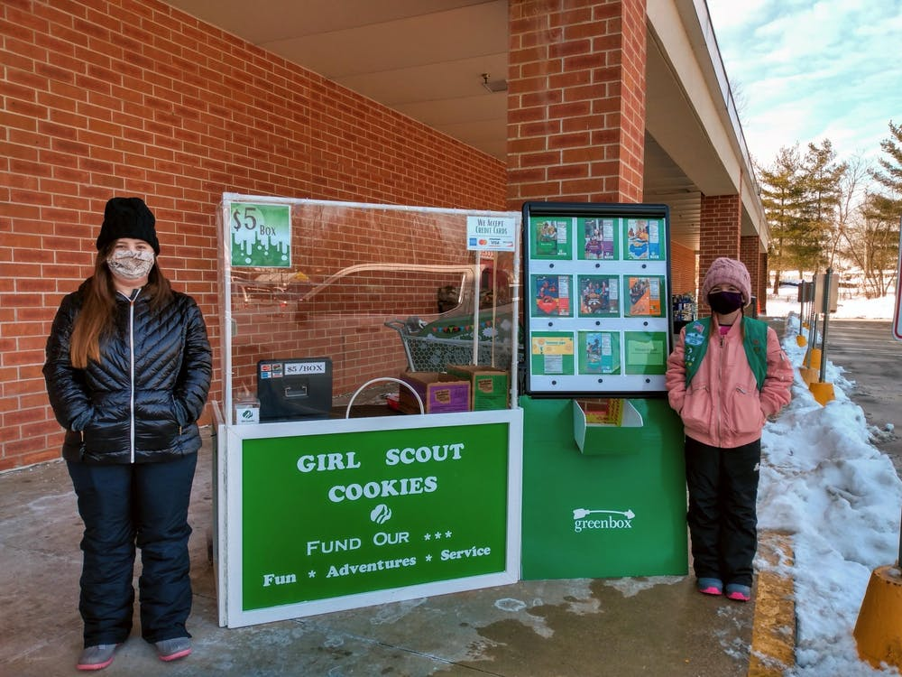 Ainsley and Wren Ferguson pose for a photo by a Girl Scout cookie selling location for troop 3154. Eight varieties of Girl Scout cookies are available for delivery on Grubhub in Bloomington.