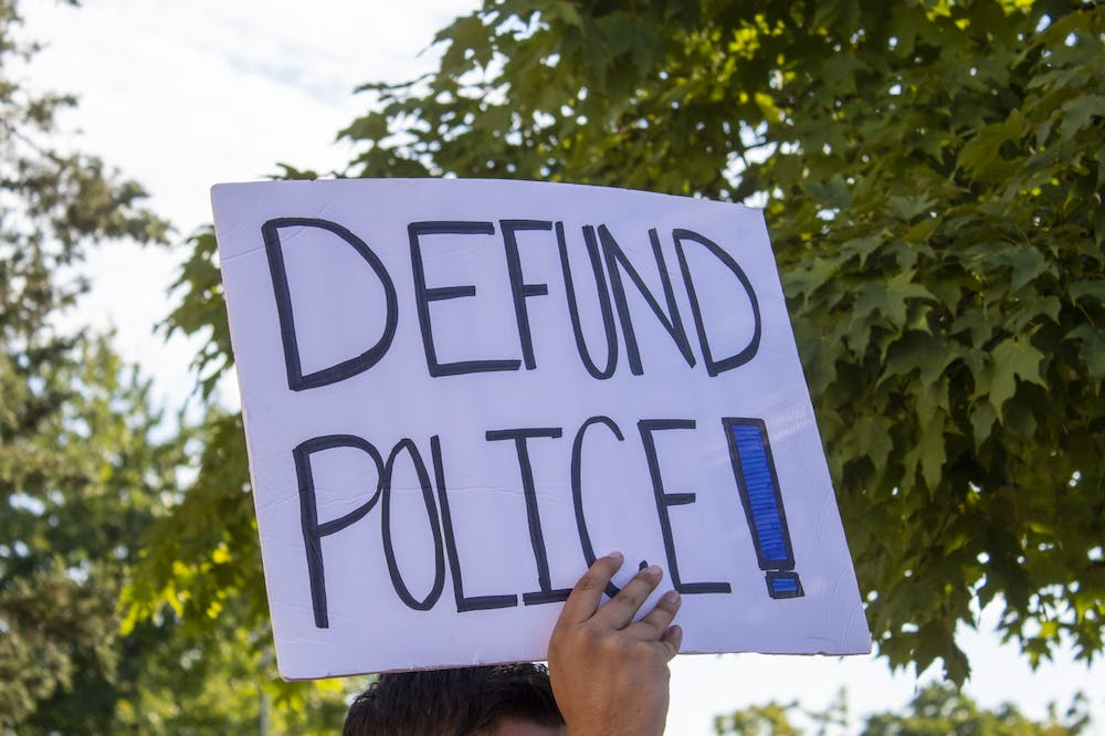 """<p>A protester holds a sign reading """"Defund Police"""" on Aug. 18 outside of City Hall. Community members have been organizing rallies during city council's budget meetings this week to encourage diverting police funding to community resources.</p>"""
