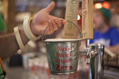 Nobody is quite sure whose idea it was to bring the buckets to Nick's. The idea for a drinking club using buckets came from a bar someone visited in Wyoming in the early 1970s. The 120 tin buckets were hung on 120 hooks above the main bar for elite regulars.