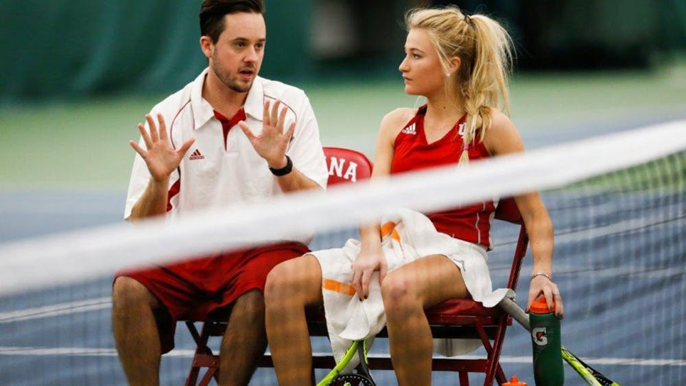 IU women's tennis assistant coach Ryan Miller sits and talks with then-sophomore Madison Appel during a match.