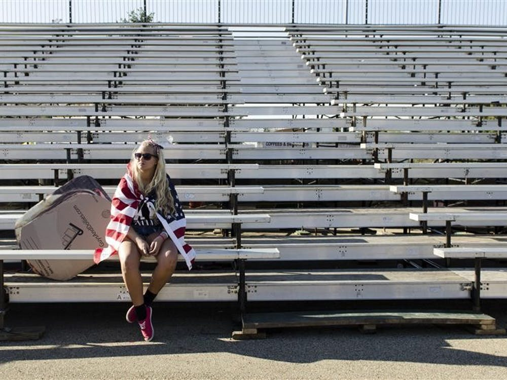 Kappa Delta sophomore Jessy Riekhof, cloacked in an American flag, sits alone in the bleachers as Bill Armstrong stadium clears Friday after the Little 500 women's race.