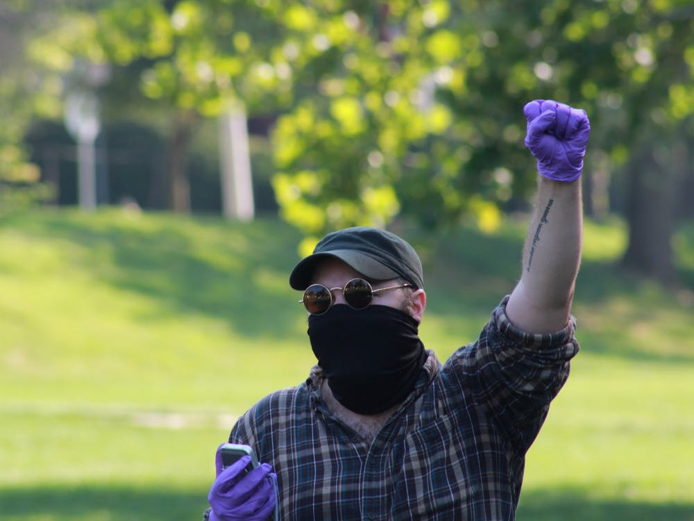 Nathan Schmidt, a graduate student in the English department, raises his fist as protesters chant Aug. 24 in Dunn Meadow.