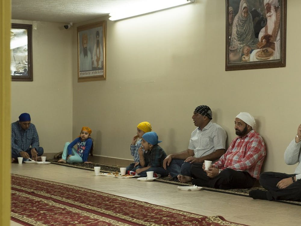 Sikhism practitioners having a meal at the basement of a Sikh Gurdwara in Fishers, Ind. They believe that having meals on the floor promotes equality.